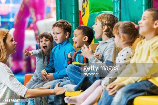 Children singing with their teacher.