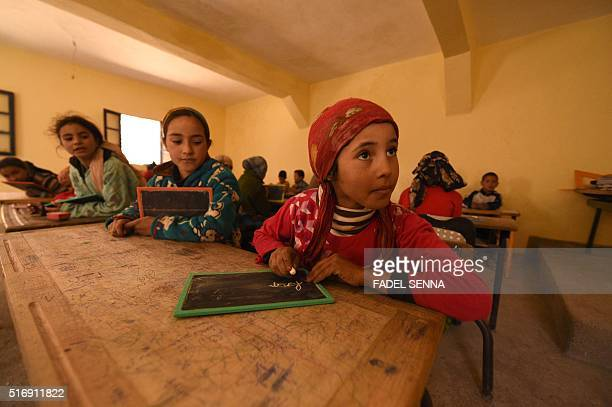 Children sit in a classroom at a school in the Moroccan village of Taghzirt in elHaouz province in the High Atlas Mountains south of the capital of...