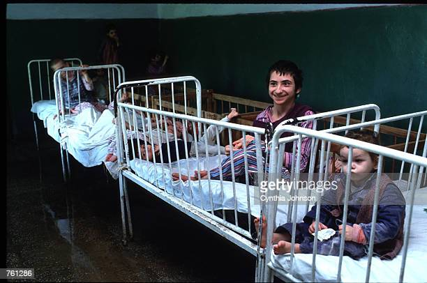 Children sit in cribs at an orphanage May 14 1990 in Vulturesti Romania The orphanage is for children who have birth defects such as retardedness and...