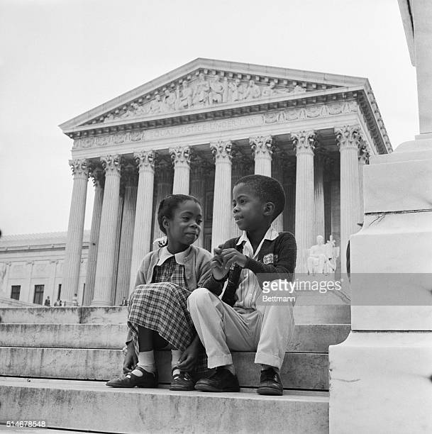 Children sit in front of the Supreme Court which is hearing arguments about the integration Little Rock Schools