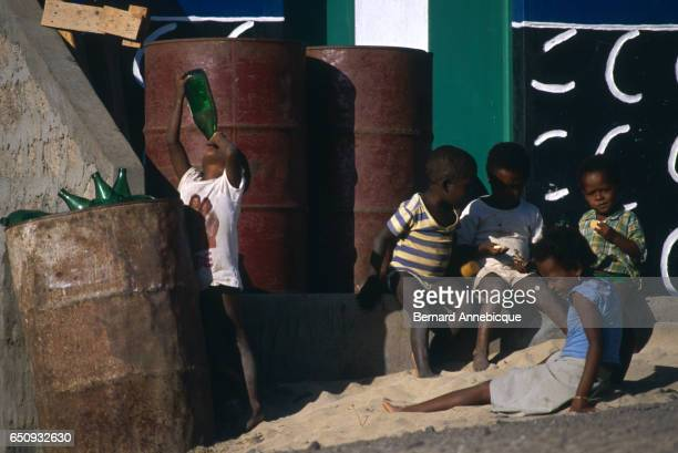 Children sit next to steel barrels as one of them drinks from a bottle | Location Sao Pedro Sao Vicente Island Cape Verde