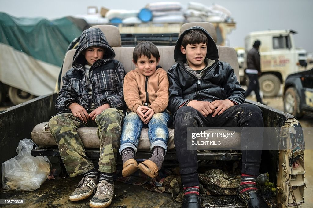 Children sit on a car as Syrians fleeing the northern embattled city of Aleppo wait on February 6, 2016 in Bab-Al Salam, near the city of Azaz, northern Syria, near the Turkish border crossing. Thousands of Syrians were braving cold and rain at the Turkish border Saturday after fleeing a Russian-backed regime offensive on Aleppo that threatens a fresh humanitarian disaster in the country's second city. Around 40,000 civilians have fled their homes over the regime offensive, according to the Syrian Observatory for Human Rights monitor. / AFP / BULENT KILIC