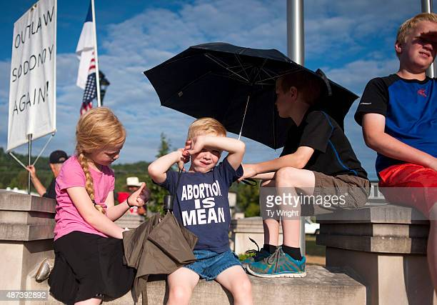 Children sit on a wall in front a protest in front of the Rowan County Courthouse on September 9 2015 in Morehead Kentucky County Clerk Kim Davis was...
