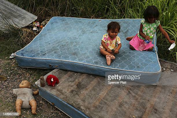 Children sit on mattresses as their home and neighborhood are forcefully dismantled in a shanty town after the government claimed that the settlement...