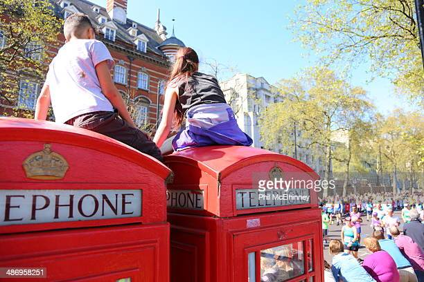 Children sit on to of a London phone box to watch the London marathon