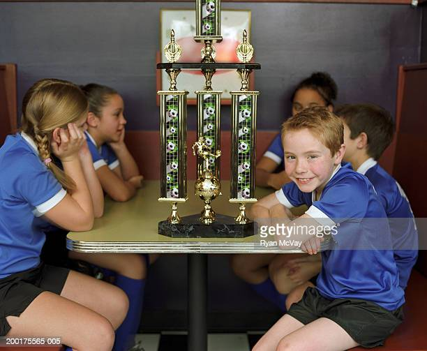 Children (10-12) sitting at table (focus on boy beside soccer trophy)