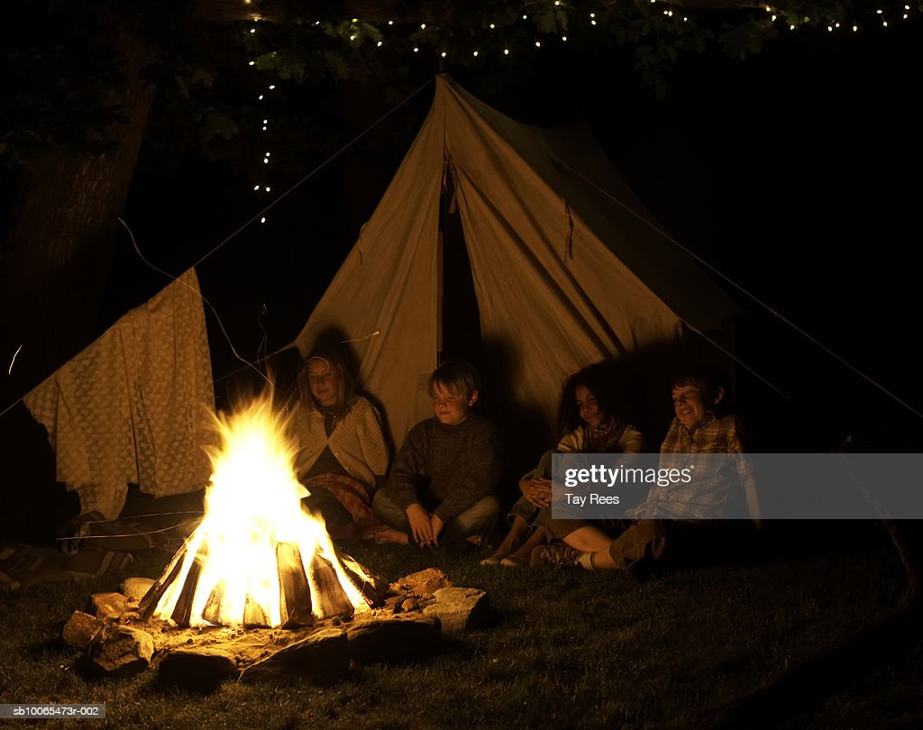 Children (6-13) sitting by camp fire at night : Stock Photo