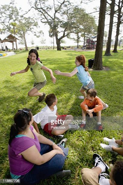 Children sitting in a circle on the grass with their teacher while two girls run around them