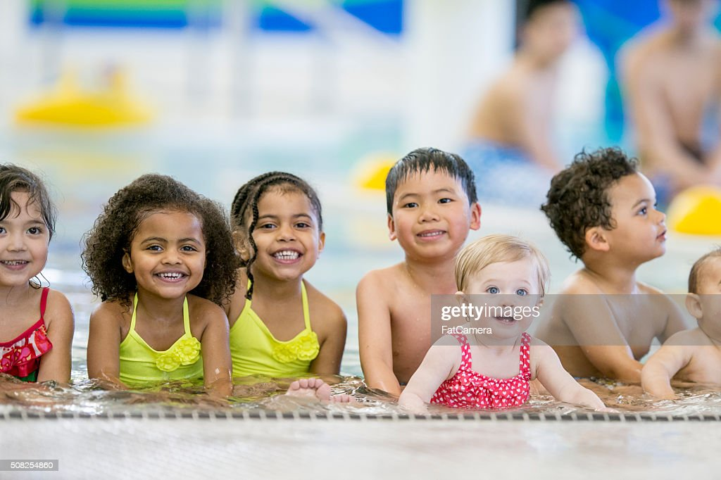 Children Sitting in a Shallow Pool : Stock Photo