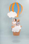 Children sitting in diy paper balloon basket