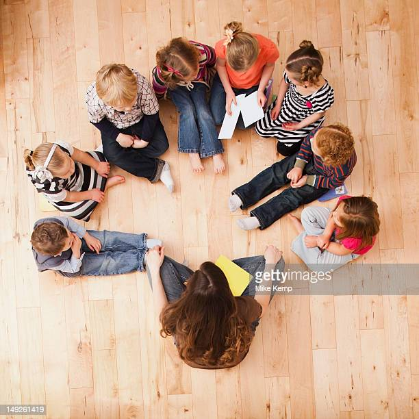 Children (2-3, 4-5) sitting in circle around teacher, directly above