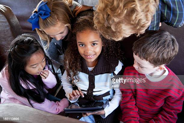 Children sitting inside school bus with digital tablet