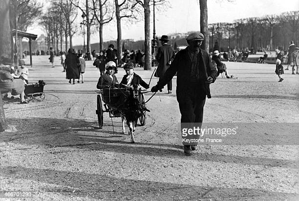 Children sitting on a cart dragged by a goat in the Luxembourg Garden in December 1929 in Paris France