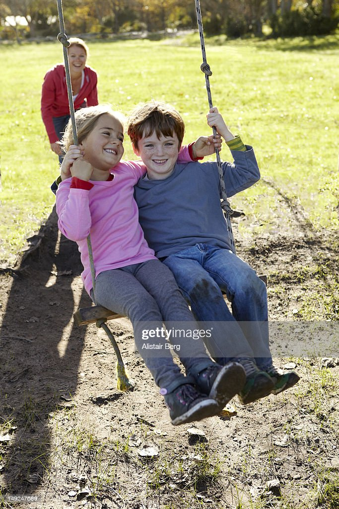 Children sitting on a swing together : Stock Photo