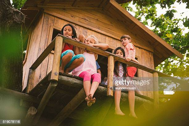 Children sitting on edge of a rustic wooden treehouse
