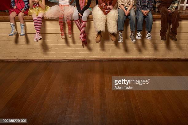 Children (5-12) sitting on edge of theatre stage, low section