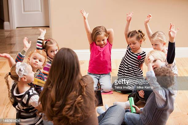 Children (2-3, 4-5) sitting on floor and raising hands