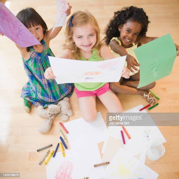 Children sitting on floor holding up drawings