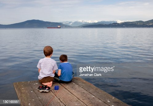 Children sitting on  pier.