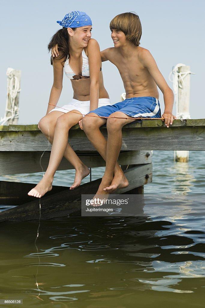 Children sitting on pier