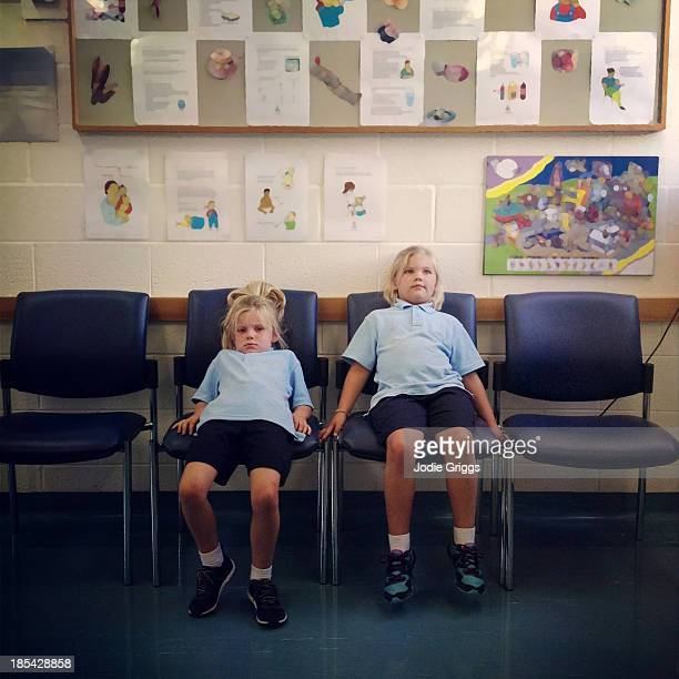 Children sitting on seats in dentist waiting room