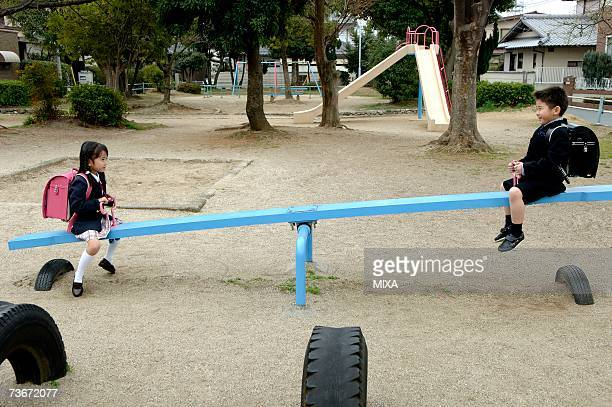 Children sitting on seesaw