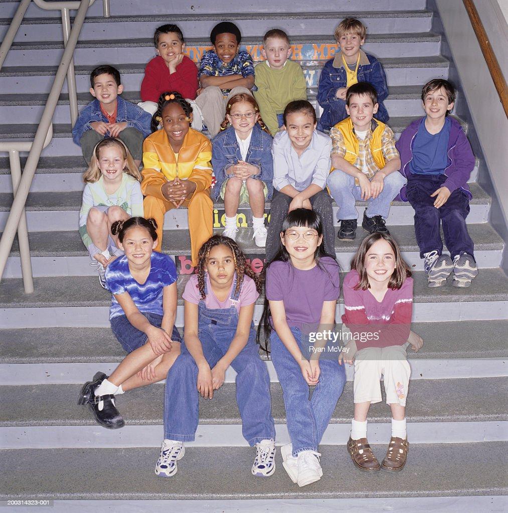Children (8-9), sitting on stairs in school, portrait : Stock Photo