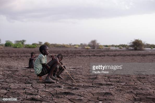 Children sitting on the Omo River bank which is slightly cracked due to the lowering of water level which supplies water to Gibe III Dam Gibe III Dam...
