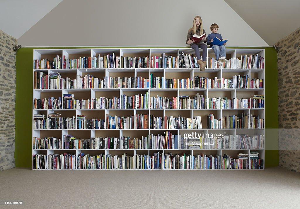 Children sitting on top of bookshelves : Stock Photo