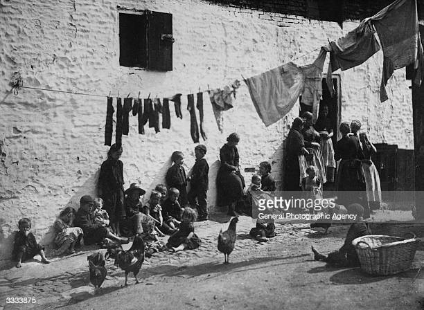 Children sitting under a washing line hanging acoss a courtyard in a slum area of London