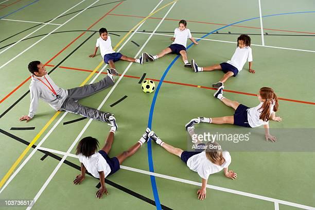Children sitting with coach in gymnasium