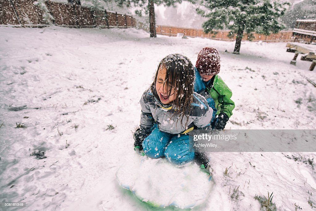 Children sled backwards in a large snow storm