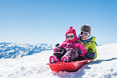 Happy little brother and cute sister enjoying sleigh ride. Smiling children sitting on the sled. Children play with bobsled outdoors in snow. Winter vacation concept.
