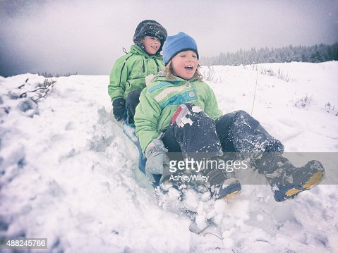 Children sledding together in snowy weather