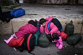 TOPSHOT CORRECTION Children sleep as they wait in the port of Piraeus after their arrival from the islands of Lesbos and Chios on February 24 2016...