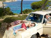 Children sleep on the hood of the car