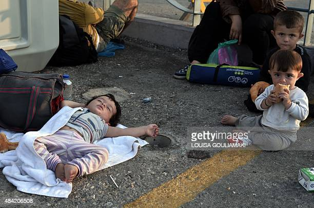 Children sleep or sit outside the port while waiting with other migrants to enter the port to board the Eleftherios Venizelos liner which will serve...