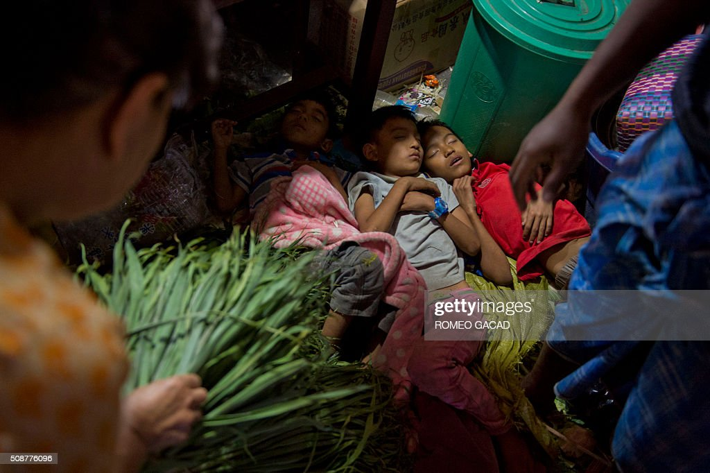 children sleeps on the ground outside the gate of a temple during last minute rush in Yangon's Chinatown district on February 6, 2016 in preparation for the Lunar New Year celebrations which falls on February 8 and will mark the start of the year of the monkey. / AFP / ROMEO GACAD