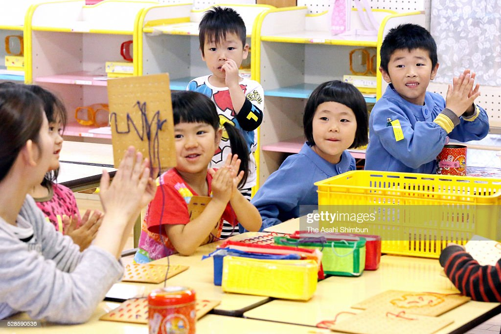 Children smile as their nursery is reopens on May 6, 2016 in Mashiki, Kumamoto, Japan.