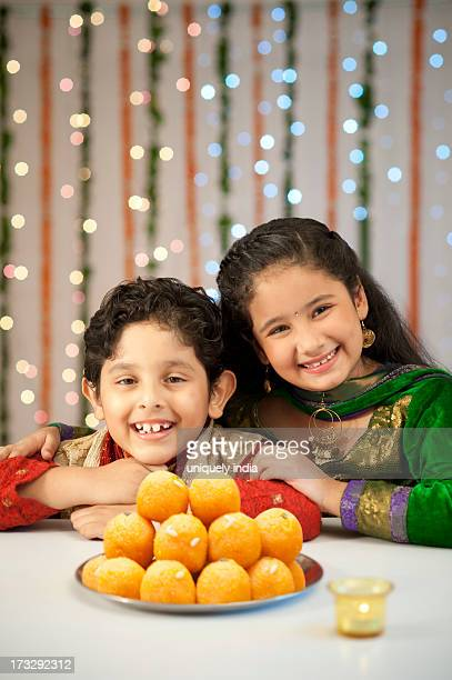 Children smiling and a plate of laddoo on Diwali