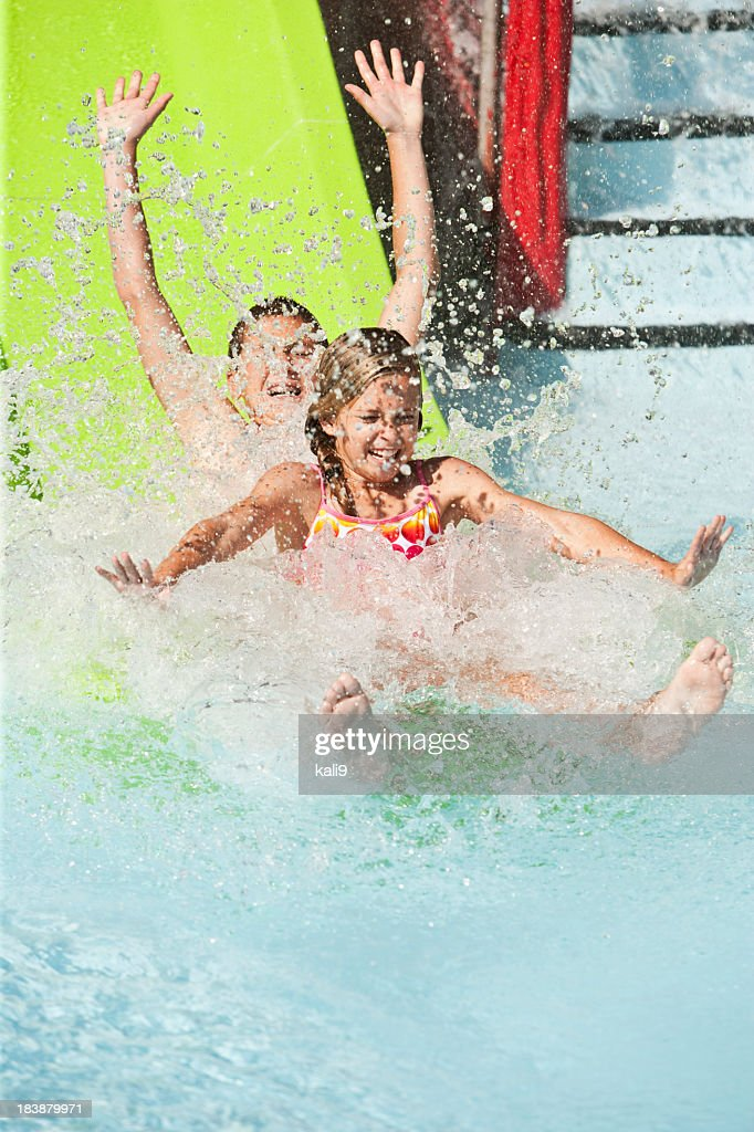 Children splashing down slide at water park : Stock Photo