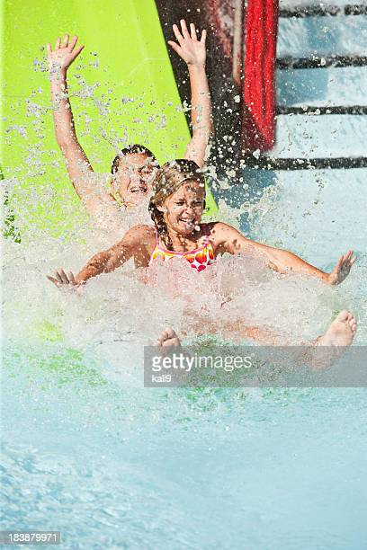 Children splashing down slide at water park