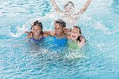 Children splashing in swimming pool.