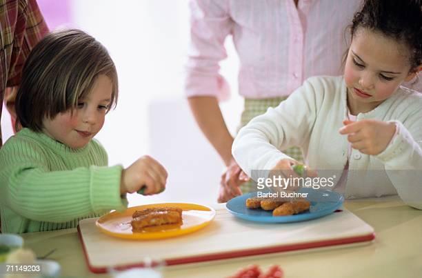 Children (4-7) squeezing lemon over fish sticks, close-up