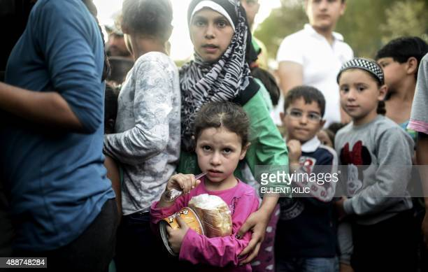 Children stand in line as Syrian refugees queue for food as they rest beside the highway on their way to the border between Turkey and Greece in...