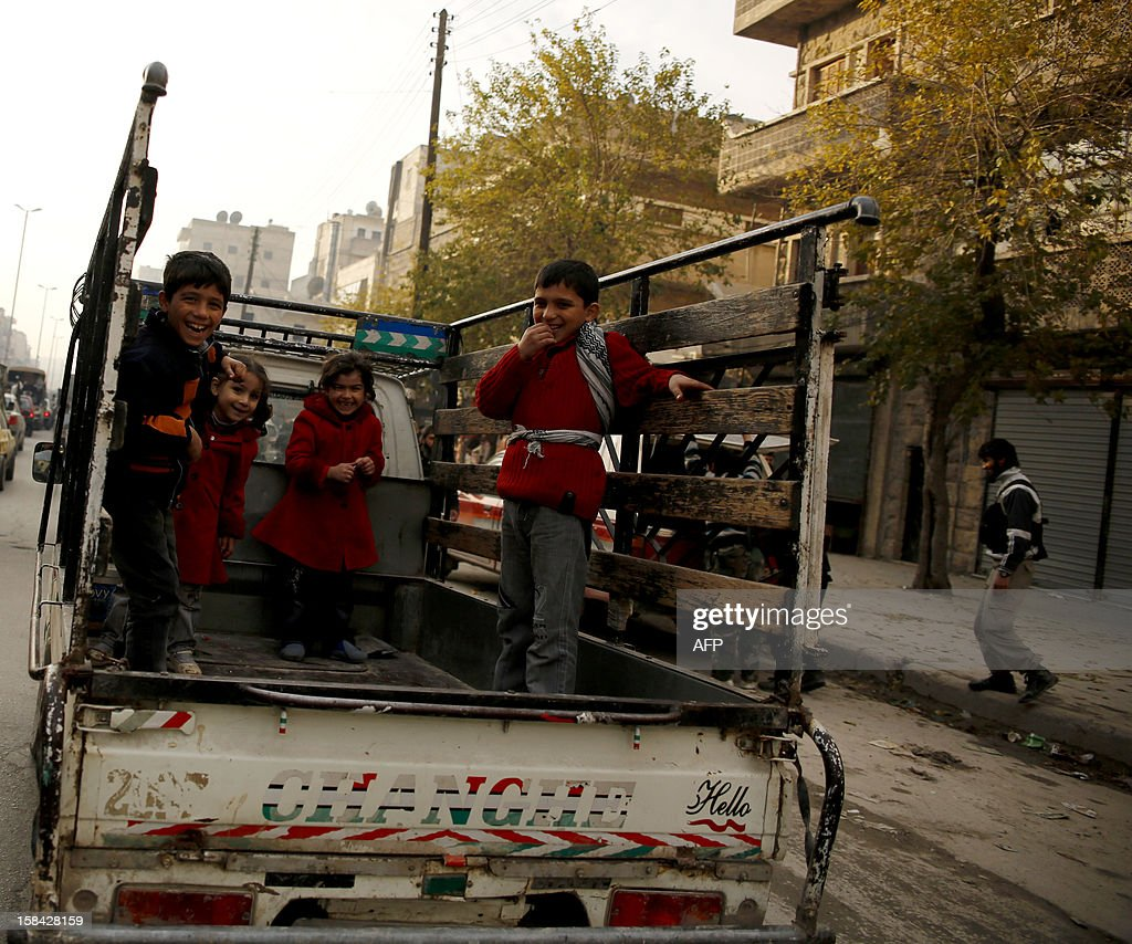 Children stand in the back of a pick-up truck in Syria's northern Aleppo province, on December 16, 2012. Syrian Vice President Faruq al-Sharaa said in an interview, to be published, that neither his government nor the rebels fighting to overthrow it can win a decisive victory in the 21-month conflict. AFP PHOTO / PRASHANT RAO