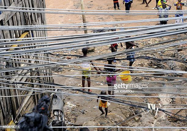 Children stand near a common courtyard under a bunch of electric lines on June 19 2014 in a poor neighborhood in the Attecoube commune central part...