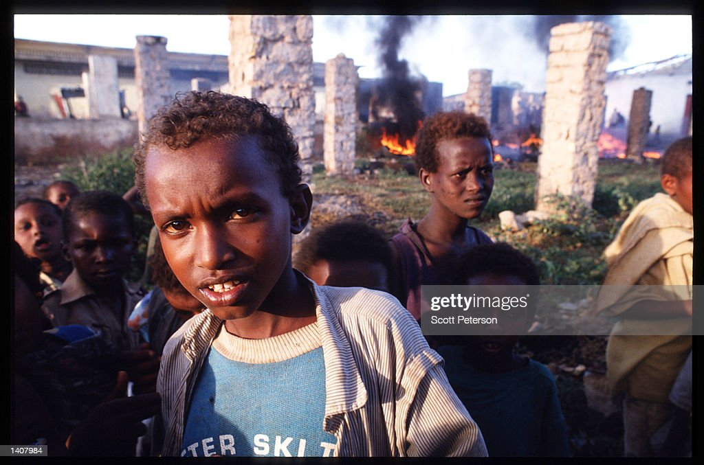 Children stand near burning debris January 15 1993 in Baidoa Somalia US troops arrived in 1992 marking the beginning of a UN peacekeeping mission...