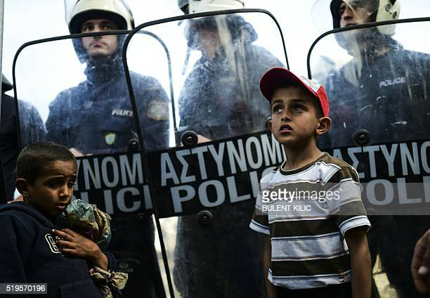 Children stand next to riot police forces during a protest held by migrants and refugees to call for the reopening of the borders at their makeshift...