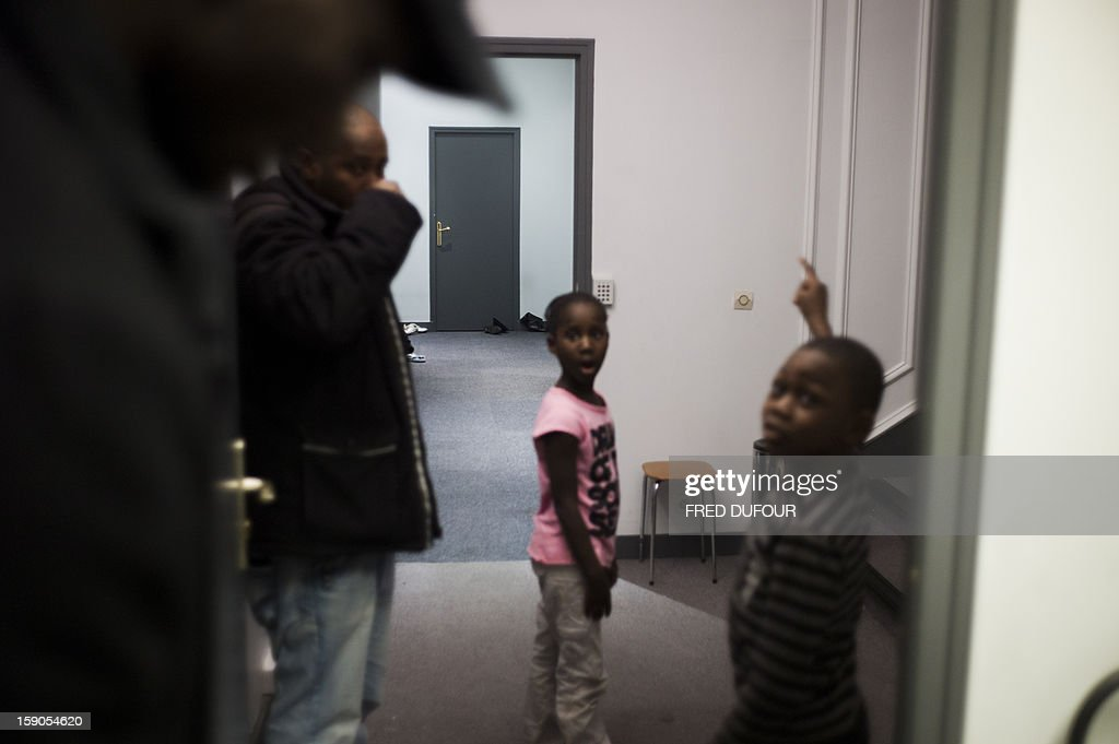 Children stand next to their father in a corridor in front of the room they occupied in a building requisitioned by French associations 'Jeudi Noir' ('Black Thursday') and 'Droit Au Logement', ('Right to Housing Association', DAL), on January 6 , 2013 in Paris. The building, situated in the 10th arrondissement of Paris is occupied since December 31, 2012.
